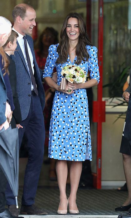 "Despite the rain, the Duchess of Cambridge looked sunny donning a label she has never worn before: Altuzarra. The mom-of-two showed off her trim figure wearing the label's blue polka-dot ""Aimee"" button-front dress, which features a V-neckline and slit. Kate accessorized the school look with a pair of tan heels and a matching clutch bag."