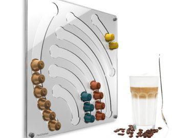 Le porte-capsule Nespresso ce support chargeur mural en Plexiglas de haute qualité va inspirer non seulement les fans de design. Shining réfraction de lumière sur les bords et le design font ce porte capsule une évidence dans votre cuisine ou votre bureau.  Il est simple et facile à charger de la partie supérieure avec des capsules Nespresso jusquà 55 de ce porte capsule. Le retrait est en dessous. Si les capsules glissent à plusieurs reprises et sont toujours prêts à portée de main. La…