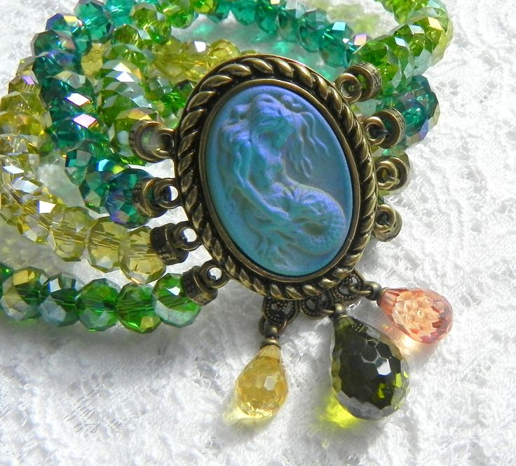 Восхитительной красоты браслет от компании Kirks Folly (США)! Барельеф русалочки светится, как будто горит изнутри,а при изменении угла наклона меняет оттенок и яркость цвета. Можно видеть богатую цветовую палитру, кристалл меняется в зелёных и фиолетовых оттенках. Кристалл выполнен из специального матированного стекла сделанного вручную, которое проходит многочасовую формовку, и является разработкой дизайнерской компании Kirks Folly. Он имеет многоговорящее патентное имя - «камень…
