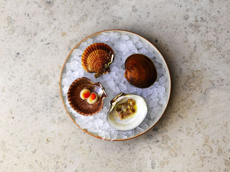 The 100-year-old mahogany clam: It is served with salted green gooseberries, pickled blackcurrant shoots, fresh blackcurrant buds and blackcurrant capers. It is seasoned with a blackcurrant wood oil and mussel juice. The mahogany clam is hand-dived in Northern Norway.