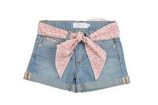 Shorts tipo jeans para niña en color azul y con una cinta en la cintura, estampada con florecitas rojas. Dos bolsillos adelante y dos atrás.