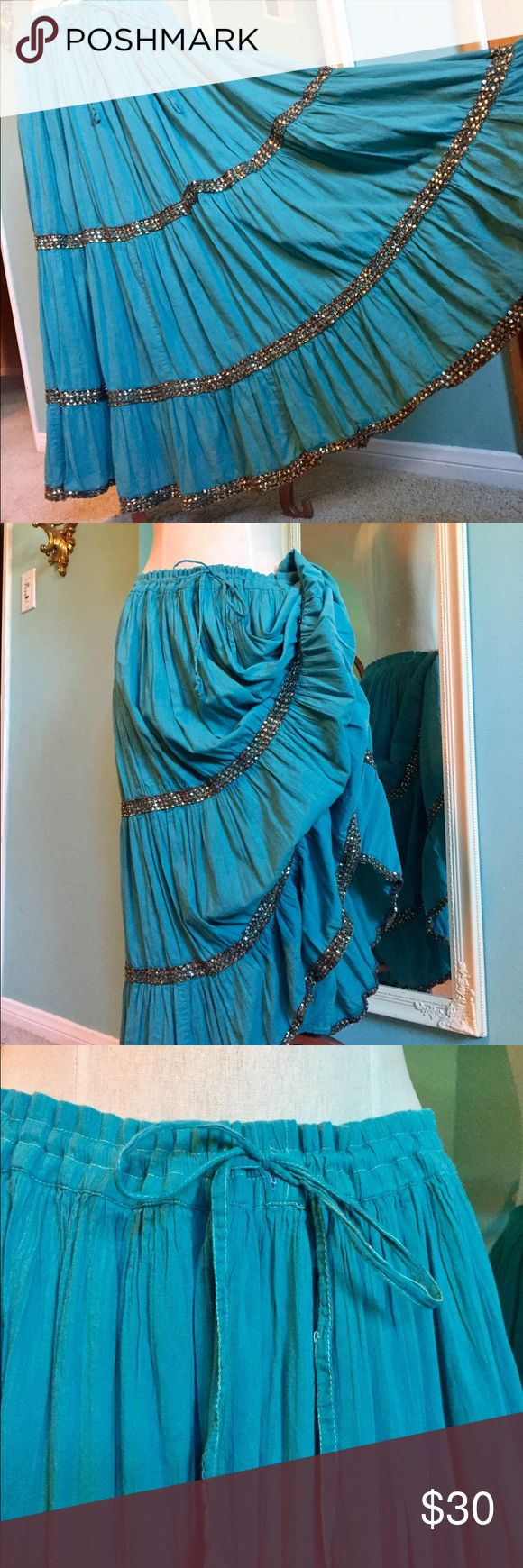 "Boho Turquoise Tiered Maxi skirt Beautiful BoHo tiered turquoise cotton maxi w/ three sparkly bands. Lots of material, great color, very flowy. Drawstring waist, no size tag: saying medium as drawstring waist expands to 44 "" and cinches to fit smaller sizes. In good pre-loved condition, two areas (see pics) on sequin bands could be tacked back down to secure but not noticeable when wearing. Lining w/ splits for movement. Last pic for inspiration. Perfect for a tropical cruise, the beach, a…"
