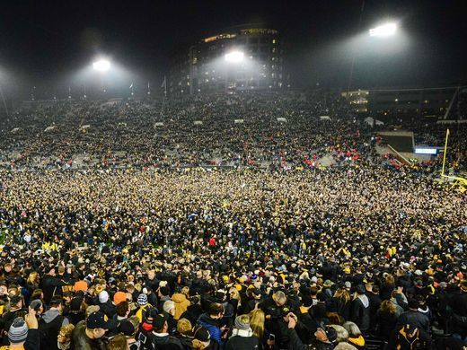 Iowa Hawkeye fans rush the field after the game against