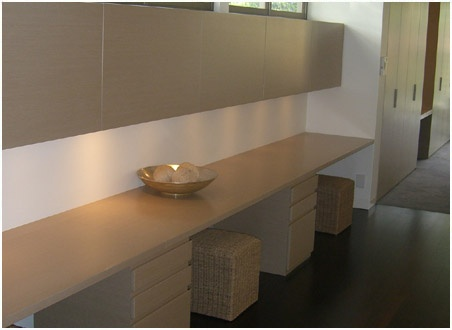 Stunning integrated home office desk with overhead awning door cabinets.