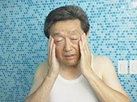 Asian man rubbing his temples in bathroom, Symptoms