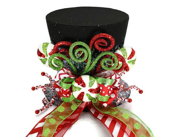 Sweeten your holiday this year with a Candy Christmas tree. This brightly colored whimsical top hat is perfect as a tree topper, table decoration, you can even use it as a vase for your centerpiece on a table. Hold flowers (vase is needed to preserve the condition of the hat) A Candy
