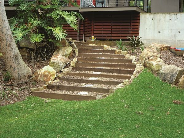 phy boulder retainng wall is used for erosion control and retaining. This wall has enabled a flat terraced area to be created with the use of sir walter grass and concrete steppers with a curved stairway and hardwood sleepers.