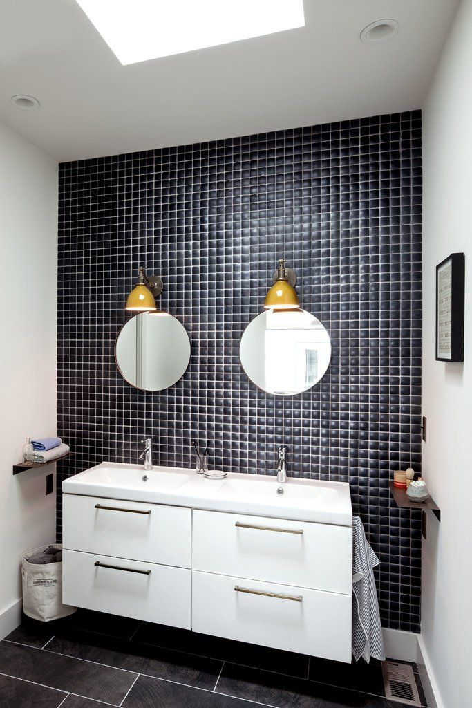 In the master bathroom, Ikea cabinets are updated with brass pulls from Schoolhouse, and one wall is covered in Pillow tile from Ann Sacks.