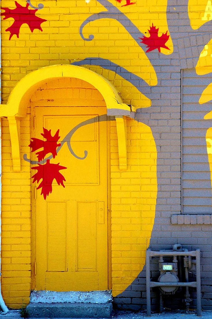 Toronto,-Ontario,-Canada - This gorgeous front door in Toronto brings the entire building into the fun, bright yellow decorative statement.