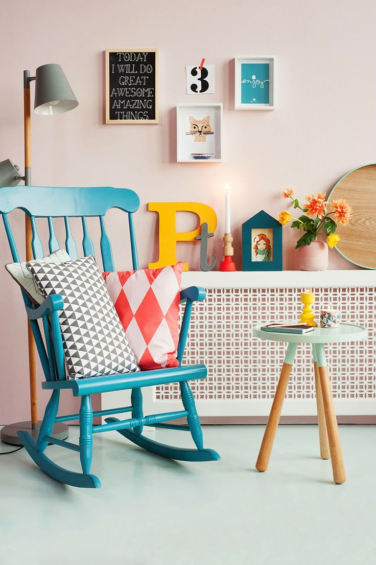 Pale pink walls with bright pops of goldenrod and teal. Great eclectic collection of art and furniture.