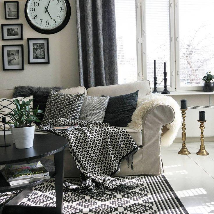 Tyynyt, viltit ja muut koriste-esineet tuovat kodikasta tunnelmaa olohuoneen mustavalkoiseen tyyliin. Huomaa myös näyttävät kynttilänjalat.