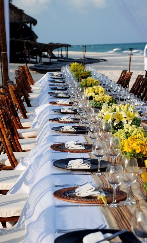 on the beach: low yellow centerpieces, wood & rattan chargers, burlap runner, bamboo chairs.