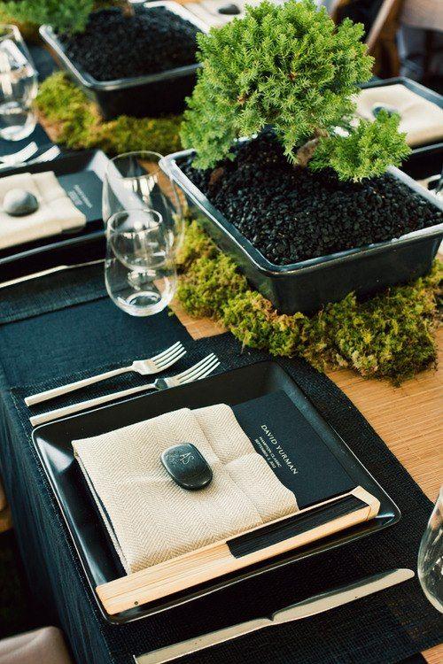 Zen-sacional Bonita mesa decorada con temática oriental. Mesa de madera al natural - camino de mesa transversal de lino - vajilla cuadrada negra mate - serilleta color arena de lino + piedra negra decorada con las siglas del comensal + cartulina negra con el menú y el nombre de los anfitriones - centros de mesa con musgo y bonsais + DETALLE REGALO abanico natural