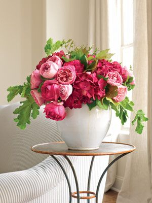 Pink garden roses, hydrangeas and huckleberry branches enhance a glazed French pot. Love this is coral colors...