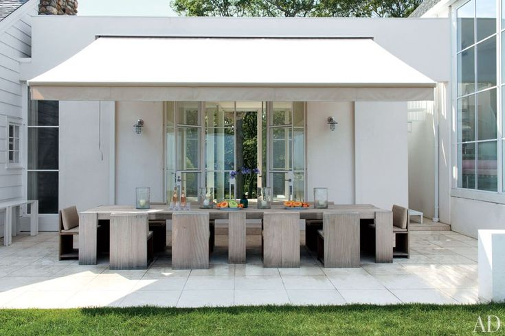 The dining terrace of a modernist Shelter Island, New York, house features chairs inspired by the work of artist Donald Judd, and a simple retractable awning.