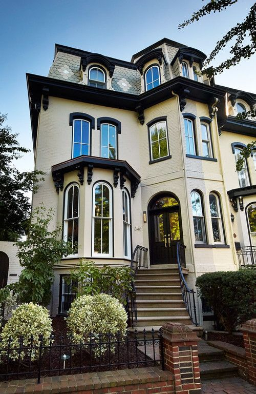 Choosing Exterior Paint Colors - Town & Country Living, Victorian house, yellow house, wrought iron fence