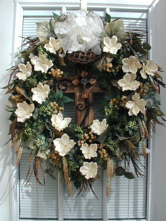 """Artificial new handmade floral door / wall wreath Approx. measurements are 23"""" wide x 26"""" long x 5-6"""" deep made on a grapevine wreath base  """"Rugged Cross"""" This design has a subtle rugged elegance to it. The large wooden cross in the center has iron scroll detail and a raised copper cross in the middle. Off-white latex magnolias surround the cross. I used delicate accents of tiny clusters of tan flowers, berry clusters, real dyed dark brown feathers, and seeded stems. The bed of greenery ..."""