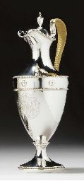 A GEORGE III SILVER HOT WATER JUG Mark of Robert Makepeace and Richard Carter, London, 1778 Of plain classical vase-shape, engraved with a monogram WMW within an oval cartouche below a band of applied palmettes, the circular foot and rim with beaded borders, the hinged cover with vase-shaped finial, the scroll handle wrapped with imitation raffia,