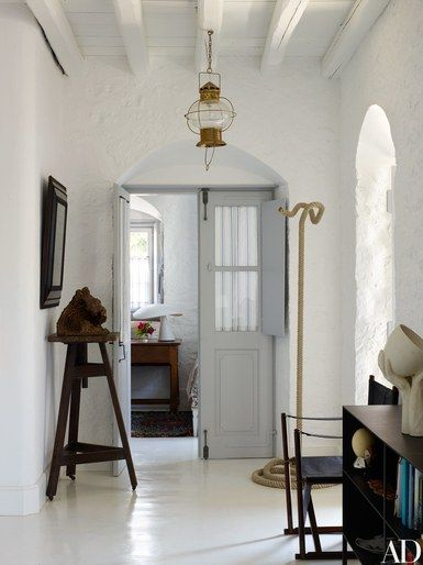 A cool palette of gray and white defines the interior spaces. Nineteenth-century ship's lantern; rope sculpture from Preface | archdigest.com