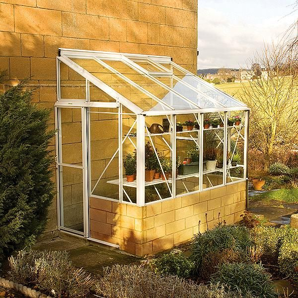 A spacious lean-to aluminium greenhouse with low-level threshold, built-in gutters and downpipes, single sliding door, toughened safety glass, ventilation and unique glazing capping and stainless steel fixings.