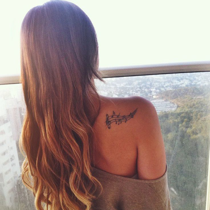 Little upper back tattoo of a music staff on Yael, representing her infinite love for music.