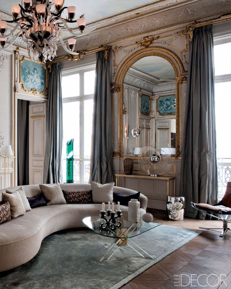 """In the living room of a Paris apartment designed by Klavs Rosenfalck, the Vladimir Kagan sofa is vintage, the gilt console is attributed to Jacques Adnet, the Murano-glass chandelier is by Aristide Najean, and the silk rug is of Rosenfalck's own design; the bottle-green columnar sculpture is by Jean-Claude Farhi, and the """"mask"""" stool is by Philippe Starck."""