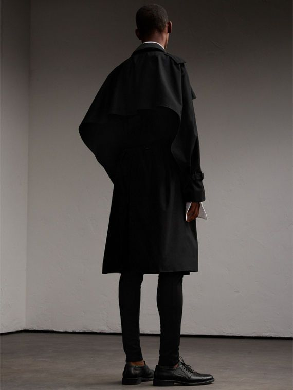 A sculptural trench coat made in England from weatherproof cotton gabardine. Taking inspiration from Henry Moore's fluid forms, the oversize storm shield extends into a sinuous panel at the sleeve, creating a dramatic cape-like effect. Our signature check features under the collar.