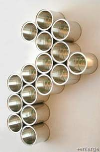 Basically these are used tin cans that have been upcycled into this cool wall art / nick-knack organizer.  Here's how it's done...    Gather up a bunch of old cans  Peel the labels off and clean them with some green cleaning products  Arrange them into whatever shape you like  Glue them together with some green glue  Dry and hang with a screw or two