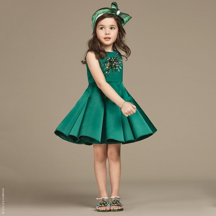 Girls gorgeous emerald green dress by Dolce & Gabbana. Made with a luxurious silk Duchess satin, which has a firmer mid-weight feel maintaining structure. The silky lined bodice is decorated with sequins in a leaf shape with caterpillar and a jewelled butterfly. The panelled skirt has a gorgeous structured flare and the dress fastens with a concealed zip at the back.