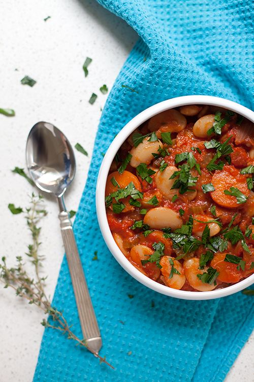Gigantes (Giant Bean Stew) [Greek Vegetarian] // 250g dried Gigantes* or Lima beans, soaked in water for at least 8 hours  1 large onion,   1 large carrot.  ~  For the stew:    1/4 c. olive oil,  1 large onion,   2 sticks of celery,   2 large carrots,   375ml vegetable stock,  1 c. of water,  2 x 400g cans of chopped tomatoes,  3 bay leaves,  1/2 cup flat leaf parsley,