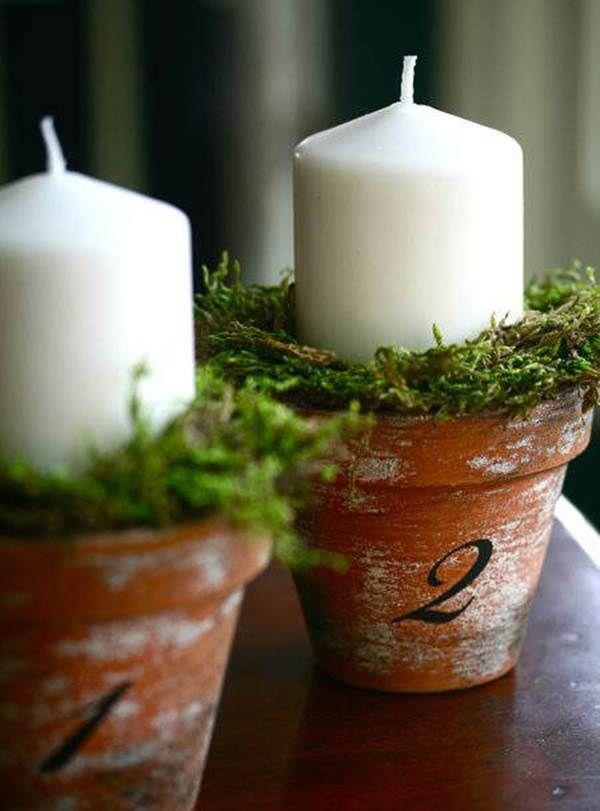 Centro de mesa navideño con pequeñas macetas y velas