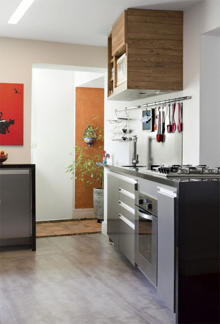 O laminado dos armários inferiores imita aço escovado. No piso, porcelanato 90 x 90 cm (Studio Emme-due). Na cuba, torneira com filtro da Deca.