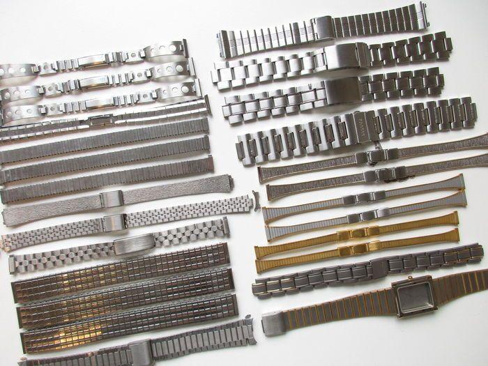 Set van 26 - stalen dames en heren polshorlogebanden - 9 t/m 22 mm - o.a. Citizen en Skagen  Set van 26 stalen dames en heren polshorlogebanden zowel dames- als herenmaten.Set bevat: - 3 x 9-11 mm stalen band (past 9 t/m 11 mm)- 2 x 10 mm vergulde band- 1 x 11-14 mm stalen kast (past 11 t/m 14 mm)- 1 x 12 mm stalen band- 2 x 12 mm stalen band met fijne vergulde streep met veiligheidsketting- 2 x 12 mm stalen band met vergulde streep- 1 x 13/10 mm stalen band (10 mm bij kastaansluiting)- 3 x…