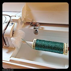 Pull metallic thread through a packing peanut to remove curls before it goes through the machine and needle.