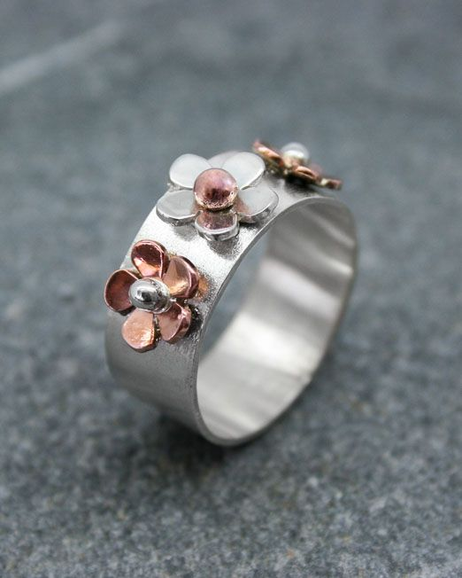 A delightful handmade silver and copper ring with three daisies.  The flat silver band is 8mm wide and has a satin finish. There is one silver flower with a copper bead in the centre and two copper flowers each side with silver centres. Can also be made in brass and silver.  #copper #daisy #flower #handmade #ring #silver #starboardjewellery #jewellery #cornwall #uk #gb #westcountry #devon #england #silversmith #pretty #jeweller #jewellers #handmadejewellery