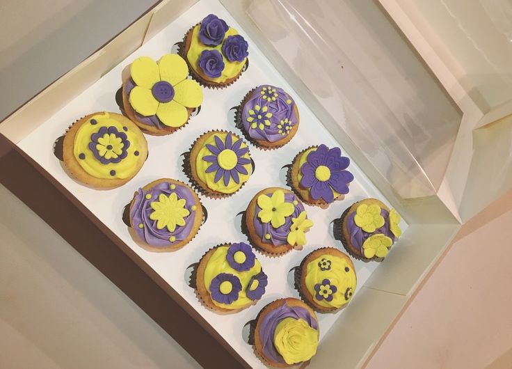 Yellow and purple flower cupcakes! So pretty!   Check out my page https://www.facebook.com/frosted.cupcakes.invercargill/