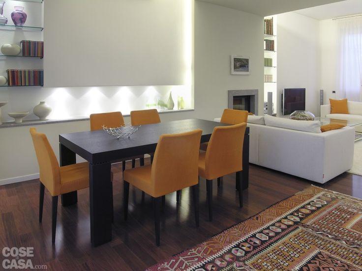 La zona pranzo, arredata in modo sobrio e funzionale, riprende il contrasto tra la tonalità scura del tavolo e del mobile contenitore in wengé, l'arancio deciso delle sedie imbottite e le tonalità neutre che caratterizzano il resto dell'ambiente