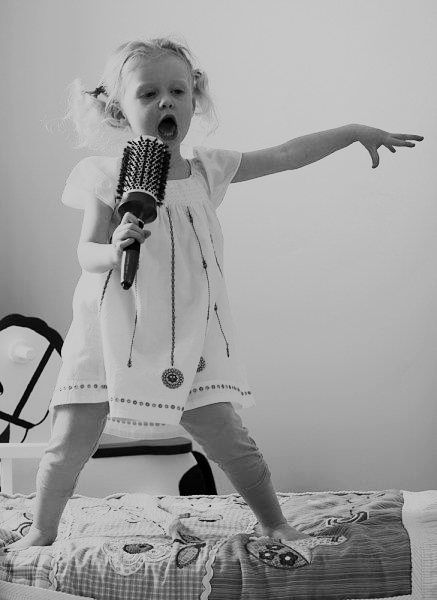 little girl singing with a hairbrush