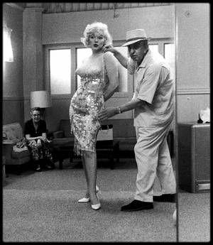 """1958 / Marilyn et Orry-Kelly lors du tournage du film """"Some like it hot"""" / MINI-BIO / Orry-Kelly grandit et étudie à Kiama en Australie, sa ville de naissance, et devient apprenti tailleur et étalagiste à Sydney. Afin de poursuivre une carrière d'acteur, il part pour New York, où il partage une chambre avec Charlie SPANGLES et Cary GRANT. Alors peintre mural dans une discothèque, il est engagé par les """"Fox East Coast studios"""" pour illustrer des génériques. Il conçoit les costumes et décors…"""