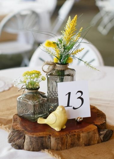Eclectic bottles with wildflowers and matching wildlife figurine set atop tree slap as guest table centerpieces. | Tara Liebeck Photography Chesapeake Virginia
