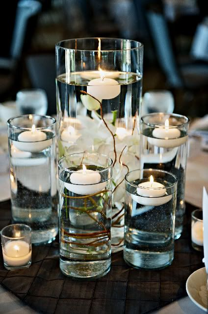 runner with mirror in center of table, topped with various cylindar vases filled with flowers/berries/etc. and water, and topped with floating candles (?!)