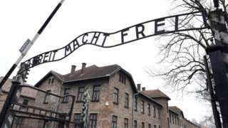 Naked demonstrators kill sheep under Auschwitz gates