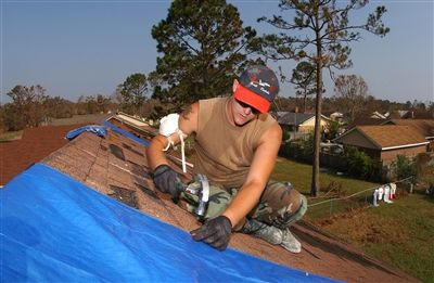 U.S. Air Force Senior Airman Gene Keller, 119th Fighter Wing, North Dakota Air National Guard, secures a covering on the roof of a home in Biloxi, Miss., Sept. 14, 2005. The home was damaged by Hurricane Katrina.