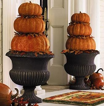 Classic decor for a front porch during the Fall or at Thanksgiving- pumpkins stacked on urns.