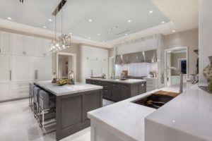 Diese geräumige Küche weiß und grau ist mit Metall gerahmten Kronleuchter akzentuiert.