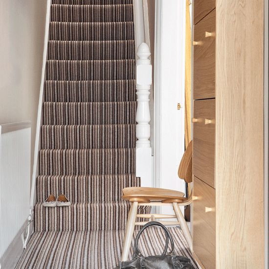Stripes hallway A striped carpet makes a striking statement on the hallway staircase and draws the eye up to the landing above. Walls are kept pale so the scheme doesn't feel too boxy. A built-in storage cupboard is ideal for tidying away shoes, hats and gloves and keeping the limited space clutter-free.