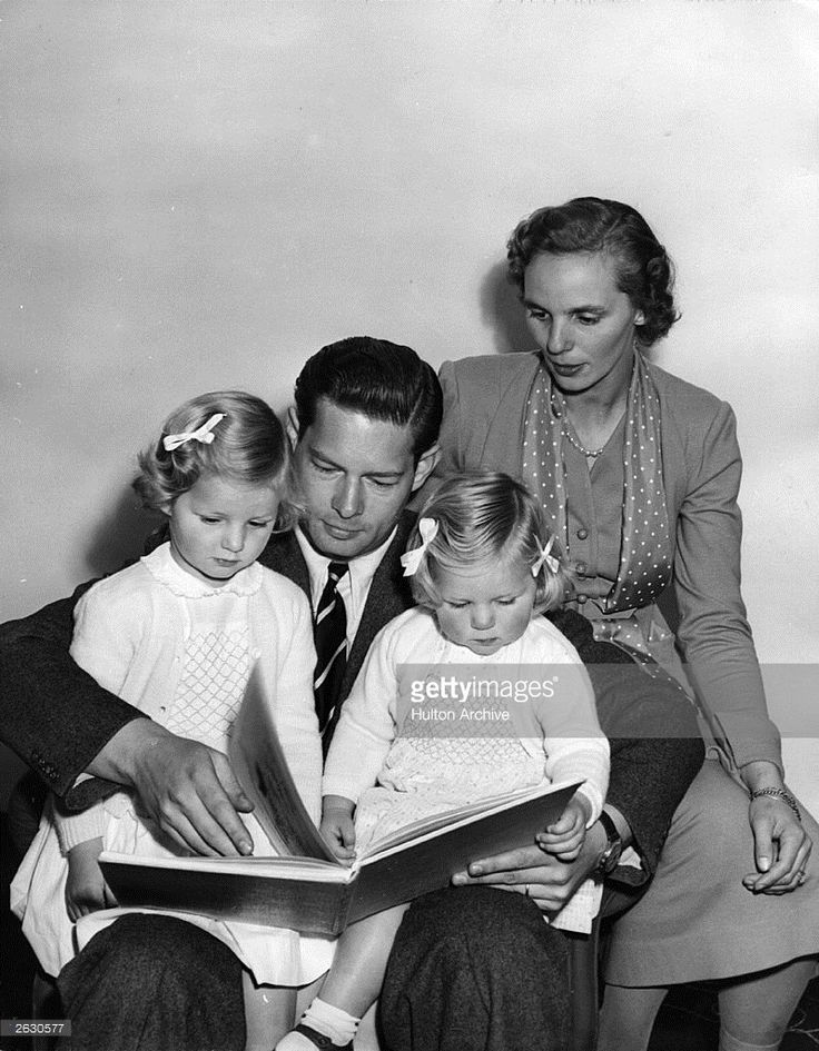 Michael, King of Romania with his wife, Princess Anne and his daughters, Princess Helen and Princess Margaret. He is reading a bedtime story.