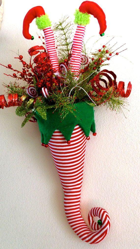 Sombrero de elfo Navidad con piernas colgando de la pared