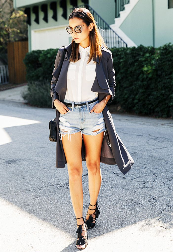 Jamie Chung wears a white sheer button-down blouse, belted cutoff shorts, a gray trench, a crossbody bag, strappy tassel heels, and Miu Miu sunglasses