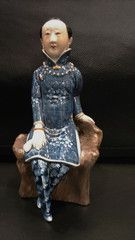 An exquisitely carved blue glaze porcelain  of a Chinese lady. Dressed in a Chinese high collar blue floral qipao and trousers her hair is tied at the back in a long bun. She wears pair of blue satin shoes on her bound feet. A gold bangle adorns each wrist. Round her neck is a little seed pearl necklace Age is new Approximate size 8 inches high x 3.5 inches wide x 3.5 inches deep